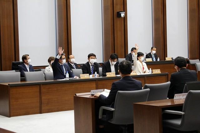 県民投票条例案を採決した防災環境産業委員会で、賛成に挙手する江尻議員と無所属の中村はやと議員